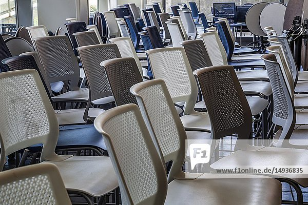 Empty chairs and tables pushed together in a lunchroom.