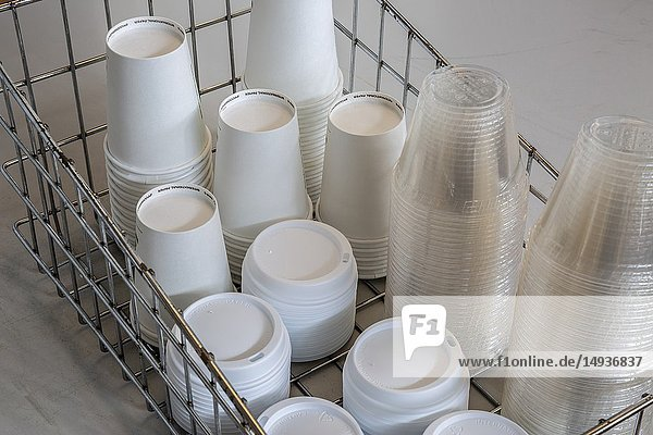 Stacks of plastic and paper cups and lids in a metal container.