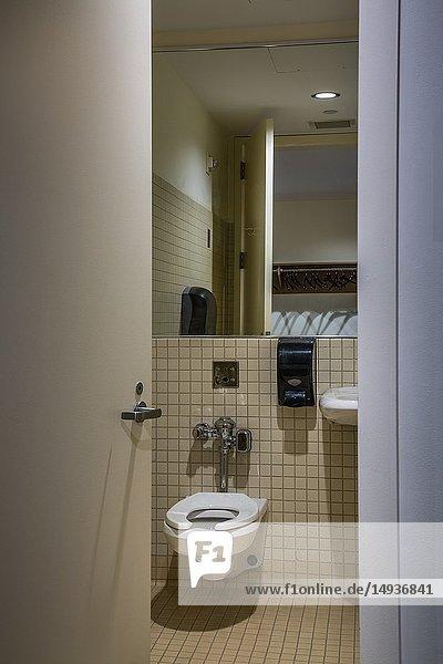Toilet in an office building seen through a partially open bathroom door.