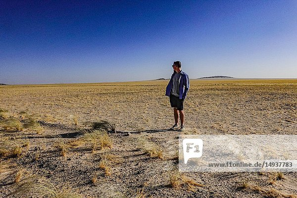 A young man stands in the desert landscape in western Namibia. Solitaire  Namibia.