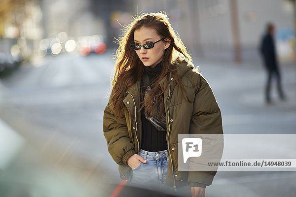 Fashionable blogger woman walking in city streets with cool individual style  in Munich  Germany