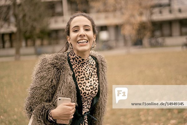 Fashionable lively woman walking outdoors in park  autumn season  wearing coat  happiness  candid emotion  unposed walking in city  Munich  Germany.