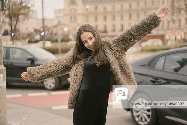 Playful happy carefree woman dancing on street in city  next to car traffic  in Munich  Germany.