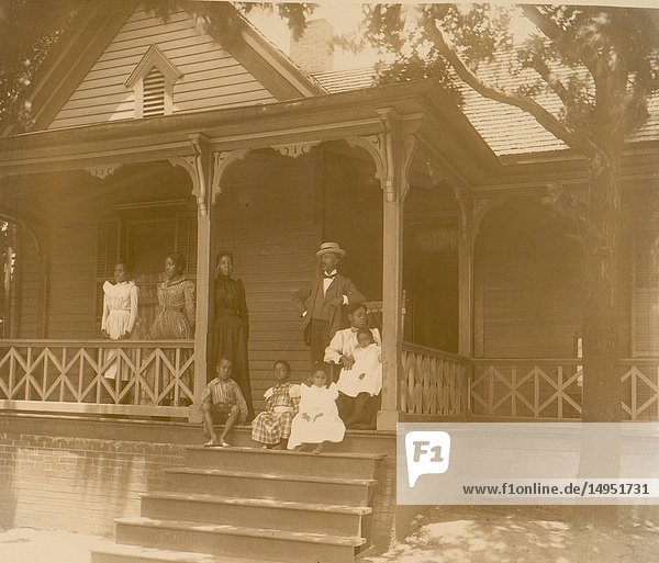 Home of an African American lawyer  Atlanta  Georgia  with men  women  and children posed on porch of house
