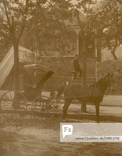African American doctor carrying small leather bag,  standing on steps to residence,  horse-drawn carriage in the foreground