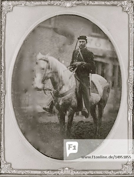 Unidentified African American soldier seated on horseback  facing left.