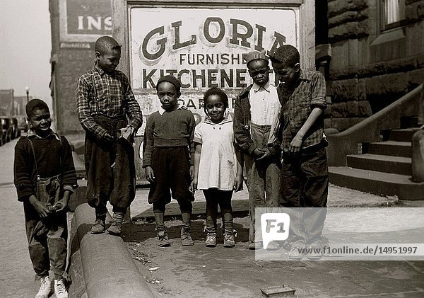 African American Children in front of a sign selling kitchenettes