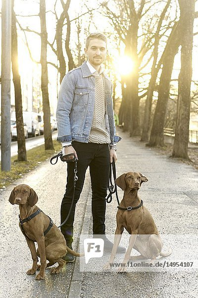 Man with dogs on leash in city  in Munich  Germany.
