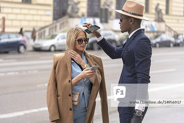 Fashionable couple with their smartphones on the street  in Munich  Germany.