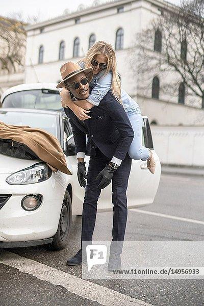 Man giving his girlfriend a piggyback ride. Munich  Germany.
