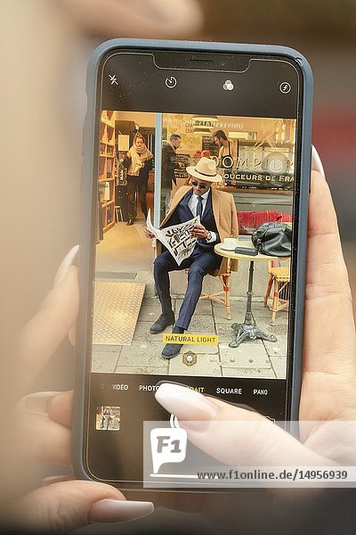 Woman taking phone photo of man in suit  reading newspaper  break  rest.
