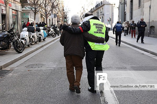 Two pensioners helping each other in the demonstration through the streets of Madrid