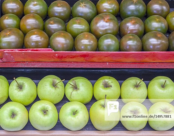 Display boxes green apples and tomatoes arranged row.