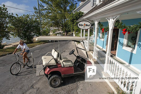 Golf car and loyalist home. Bay Street. Dunmore Town,  Harbour Island,  Eleuthera. Bahamas.