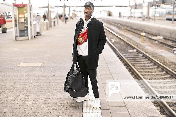 Young man standing at platform at trainstation in Munich  Germany.