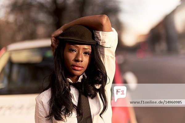 Fashionable woman at street in evening light  wearing retro business look  African Angolan descent  in Munich  Germany.