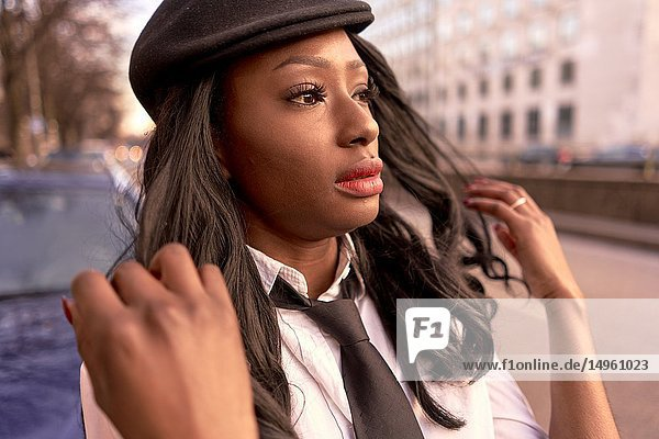 Stylish woman in evening sunlight at street  looking aside  retro business outfit  individual look  African Angolan descent  in city Munich  Germany.