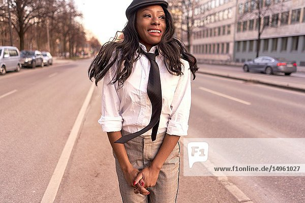 Happy stylish woman jumping in evening sunlight at street  looking aside  wearing retro business outfit  individual look  African Angolan descent  in city Munich  Germany.