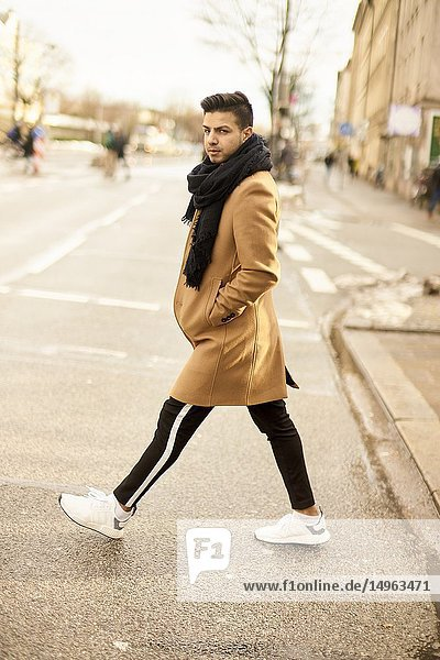 Young fashionable man walking on street in city  male blogger with style  in Munich  Germany.
