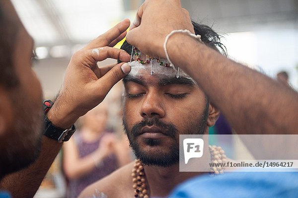 Singapore  Republic of Singapore  Asia - During the Thaipusam festival at the Sri Srinivasa Perumal Temple in Little India  a Hindu devotee has the skin of his forehead pierced with metal pins while he prepares himself for the 4 kilometer long procession to the Sri Thendayuthapani Temple.