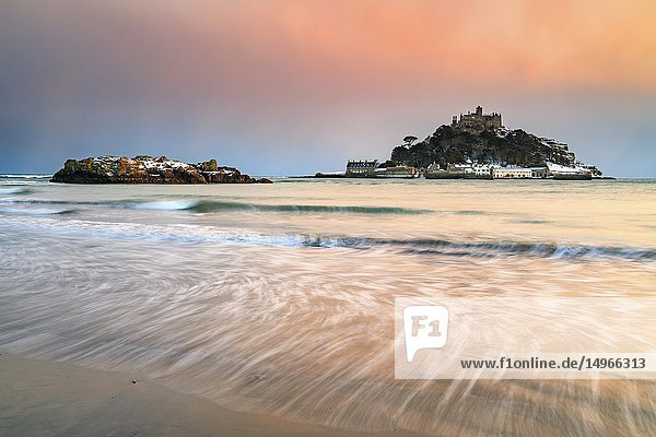 St Michael's Mount captured at sunset from the beach at Marazion in Cornwall after a snowfall in February. A long shutter speed was used to blur the movement of the water in a receding wave.