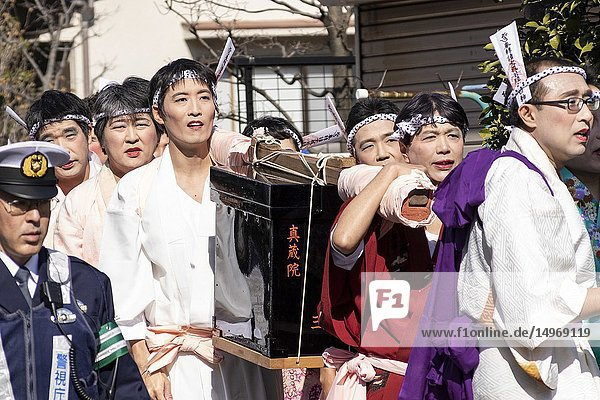 February 24  2019  Tokyo  Japan - Participants dressed in women's kimonos and wearing makeup  run from house to house to chase away evil spirits during the Ikazuchi no Daihannya festival. Festival volunteers carry 6 containers from the Shinzoin Temple around the neighborhood to chase away evil spirits. The origins of this annual event are disputed  but the legend tells the priest of Shinzoin Temple visited house to house to prevent the spread of cholera during the late Edo era. Another legend of a man who lived in the neighborhood dressed in women's kimono to scare away the bad spirits for his sister who was suffering from tuberculosis.