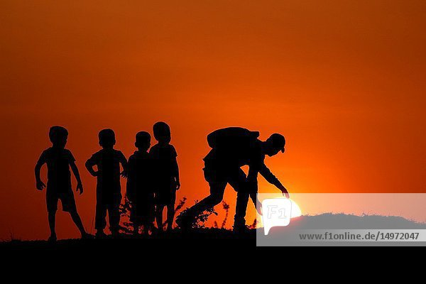Silhouette of man with the kids touching Sun  Maharashtra  India.