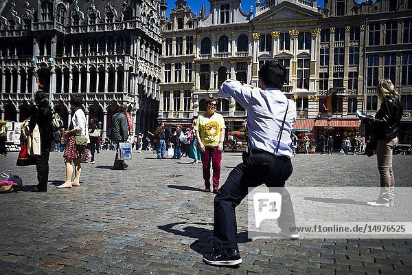 Tourists take photographs in the Grand Palce.