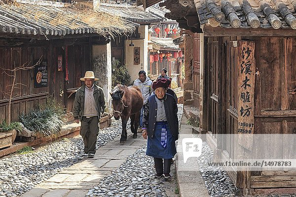 Shaxi  China - February 22  2019: Horses riding in the center of Shaxi old town at dusk.