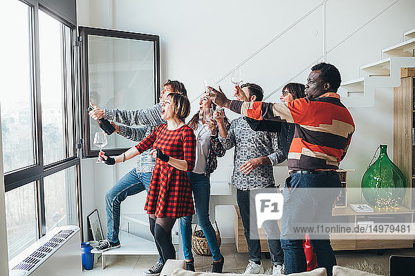 Friends taking selfie by window at party