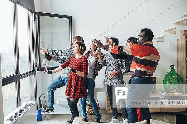 Freunde nehmen sich auf einer Party am Fenster ein