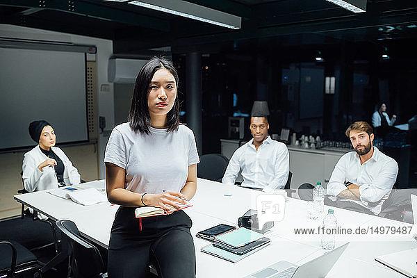 Junge Geschäftsfrau vor dem Team bei Konferenztisch-Sitzung  Porträt