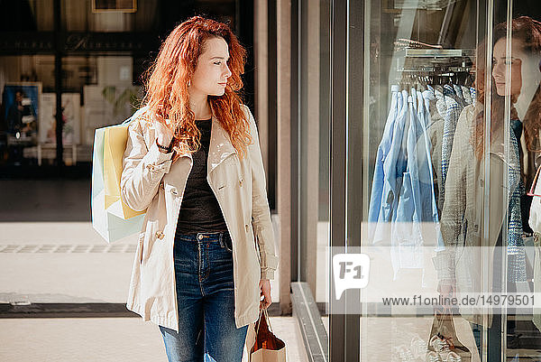 Female shopper looking into window of fashion boutique