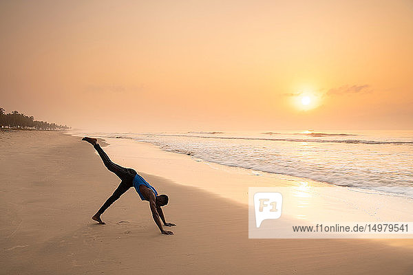 Man practising yoga on beach
