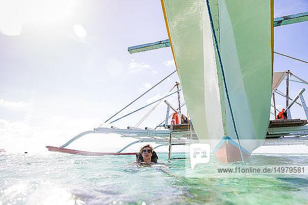 Frau schwimmt in der Nähe eines vertäuten Bootes  Insel Ginto  Linapacan  Philippinen