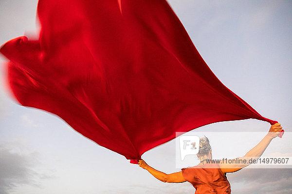 Frau hält rotes  im Wind flatterndes Tuch hoch