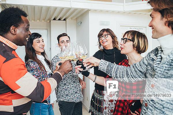 Friends toasting white wine in loft office