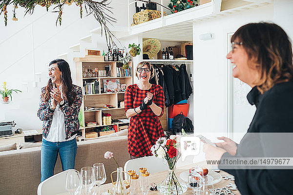 Friends clapping hands at celebration in loft office