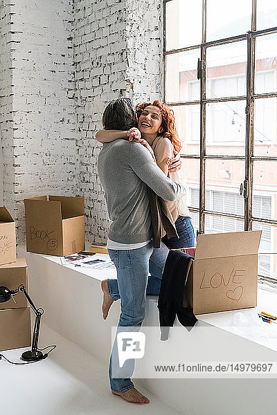 Romantic couple moving into industrial style apartment  hugging each other