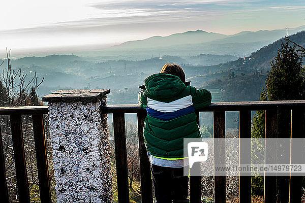 Junge blickt vom Balkon auf die Landschaft des Bergtals  Rückansicht  Piani Resinelli  Lombardei  Italien
