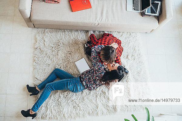 Woman kissing friend's cheek on floor in loft office