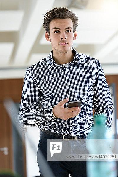 Geschäftsmann mit Smartphone im Büro