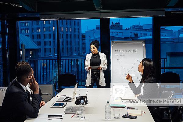 Geschäftsfrau verwendet digitales Tablett bei Büropräsentation
