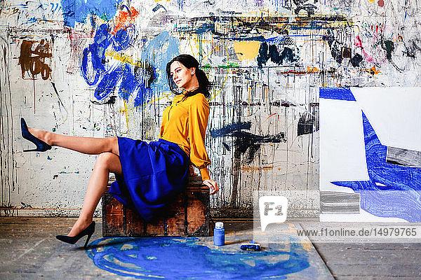 Frau posiert mit Graffiti vor der Wand