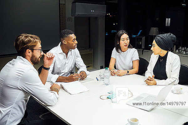 Businessmen and women having discussion during conference table meeting