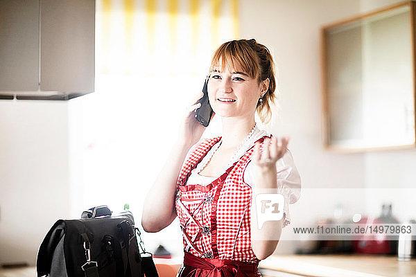 Frau benutzt Smartphone in der Küche