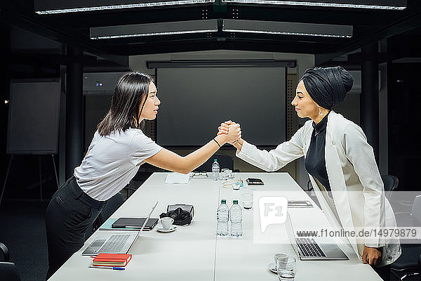 Businesswomen shaking hands over conference table