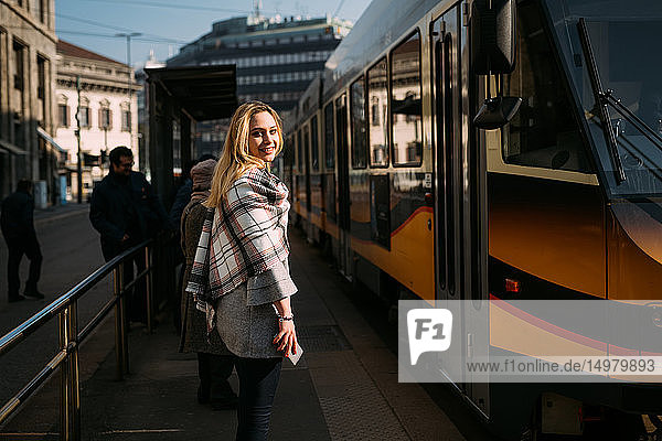 Young woman looking over her shoulder at tram station  portrait  Milan  Italy