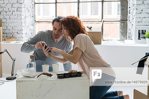 Couple moving into industrial style apartment  kneeling using smartphone touchscreen