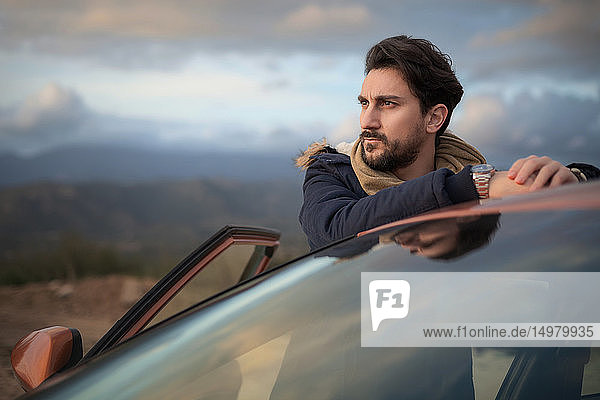 Man resting against car on roadside  enjoying view on hilltop